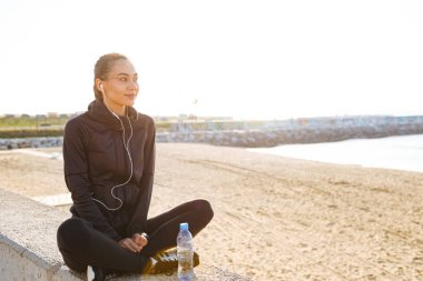 Photo of young asian sports woman sitting outdoors listening music looking aside.