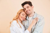 Detailní portrét šťastný muž a žena v základní oblečení objímání spolu se zavřenýma očima, samostatný béžové pozadí