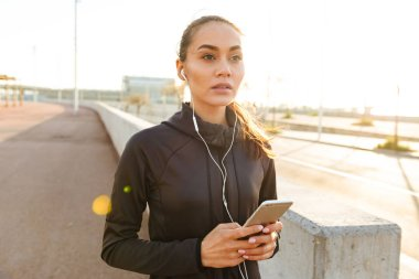 Image of serious young asian sports woman walking outdoors listening music using mobile phone.