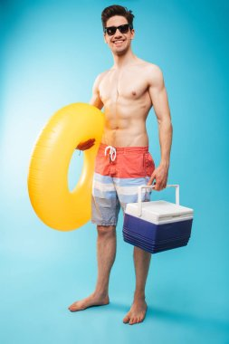 Full length portrait if a cheerful shirtless man in swimming shorts holding cooler bag and inflatable ring over blue background