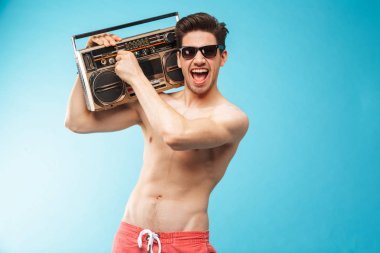 Portrait if a cheerful shirtless man in swimming shorts holding tape recorder and singing over blue background