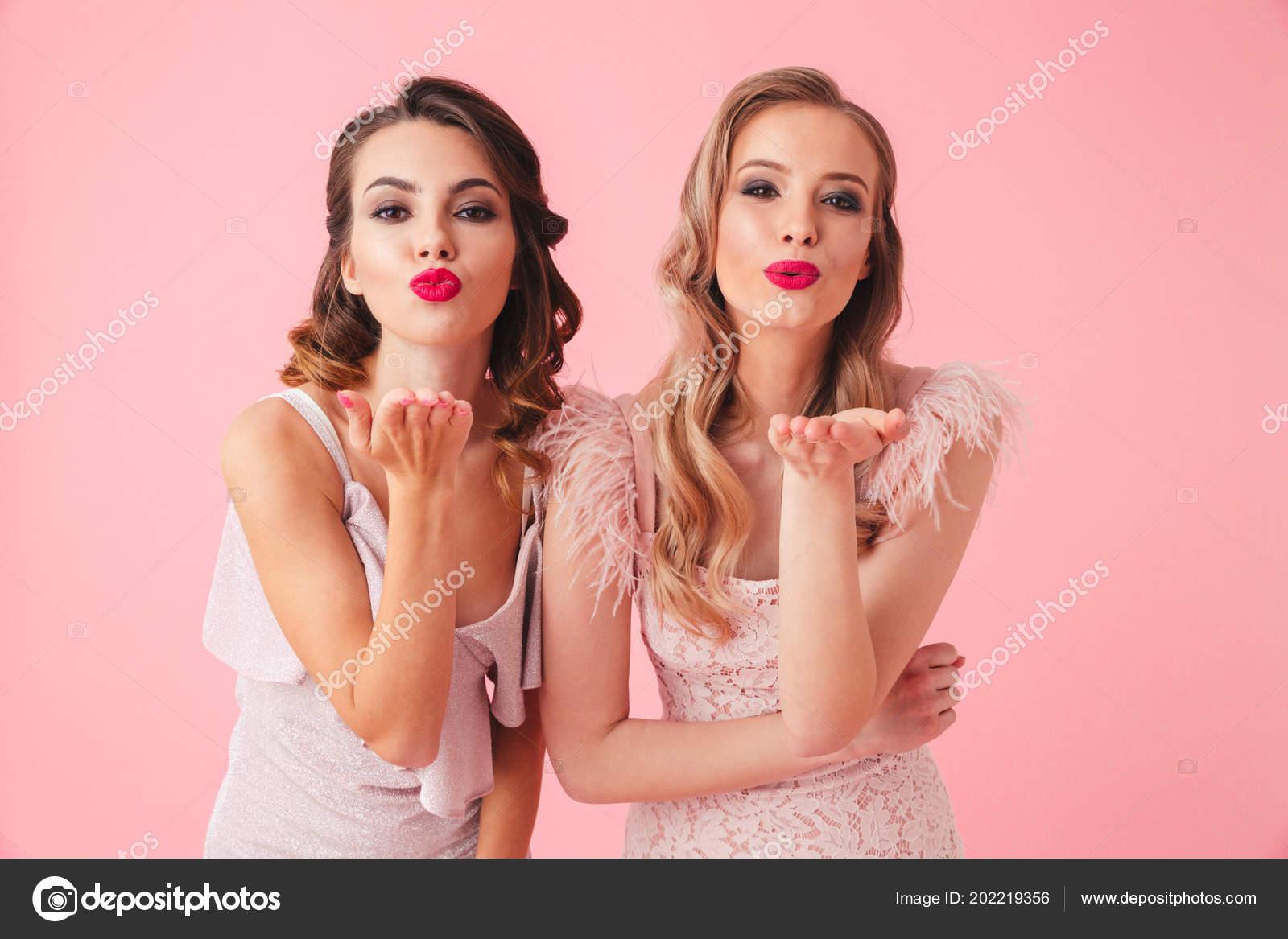 7710dfef45e7 Δύο γυναίκες σε φορέματα ποζάρει μαζί ενώ στέλνει αέρα φιλιά και  εξετάζοντας τη φωτογραφική μηχανή σε ροζ φόντο — Εικόνα από ...