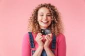 Portrét radost mladá dívka s kudrnatými vlasy drží kreditní karty izolované růžové pozadí