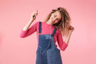 Portrait of happy young girl with curly hair listening to music with mobile phone isolated over pink background