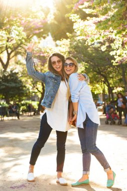 Image of two amazing happy women friends outdoors showing peace gesture looking camera.