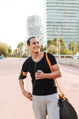 Image of happy young strong sports man outdoors walking using mobile phone listening music.