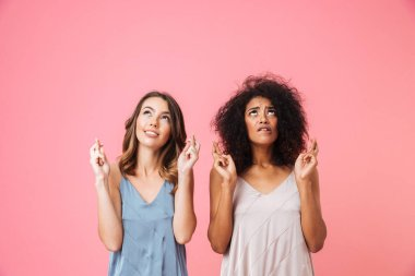 Two worried young girls dressed in summer clothes holding fingers crossed for good luck and looking up isolated over pink background