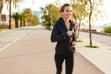 Image of happy young sports woman running outdoors on the street listening music with earphones.