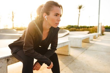 Picture of serious young sports woman sitting outdoors listening music with earphones.
