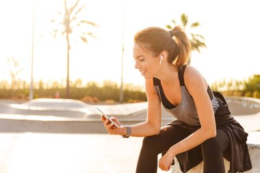 Image of happy sports lady outdoors listening music with earphones using mobile phone.