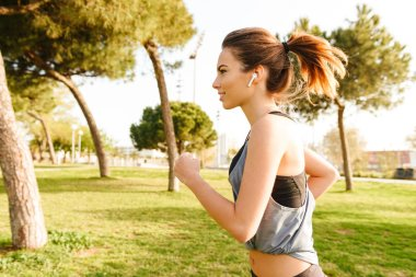 Photo of amazing young sports woman running outdoors on grass in park listening music with earphones.
