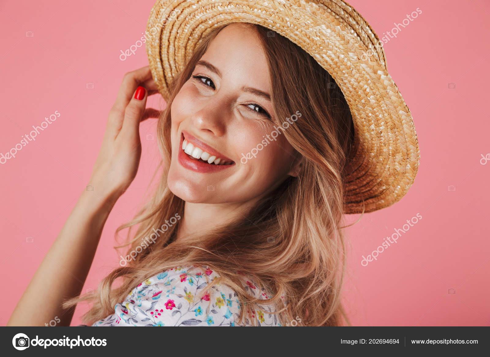Cerca de retrato de una mujer joven que en verano vestido y sombrero de  paja posando y mirando a cámara aislada sobre fondo rosa– imagen de stock 6b66df35b52