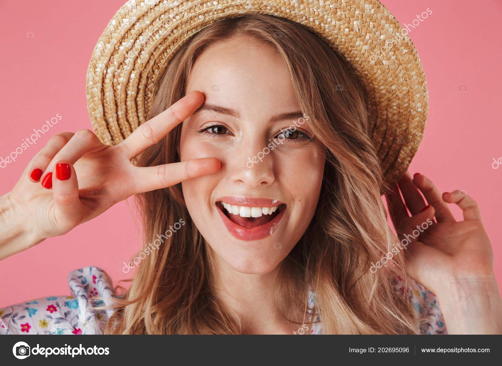 Cerca de retrato de una mujer joven feliz en verano vestido y sombrero de  paja mostrando el gesto de la paz aislado sobre fondo rosa– Imagen de  Archivo 29f9067f0d4