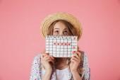 Fotografie Porträt einer hübschen jungen Frau mit Strohhut, die einen Frauenkalender in der Hand hält und isoliert über rosa Hintergrund nach oben blickt