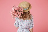 Fotografie Back view portrait of a young woman in summer dress and straw hat holding carnations bouquet isolated over pink background