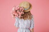 Fényképek Egy fiatal nő, nyári ruha és a gazdaság szegfű csokor rózsaszín háttér felett elszigetelt Szalmakalapot hátsó nézet portréja