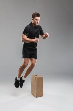 Full length portrait of a focused young sportsman jumping over a wooden box isolated over gray background