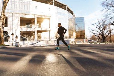 Portrait of young sportsman in earphones jogging outdoors