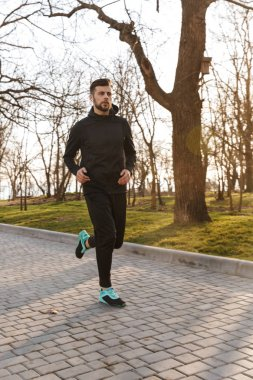 Portrait of confident young sportsman in earphones jogging outdoors