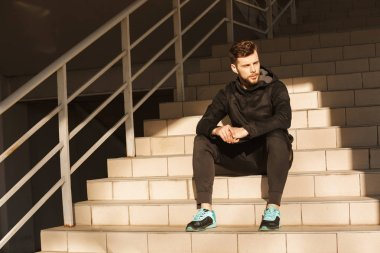 Portrait of a serious young sportsman in earphones resting while sitting on stairs outdoors