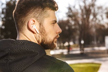 Close up of a focused young sportsman in earphones outdoors