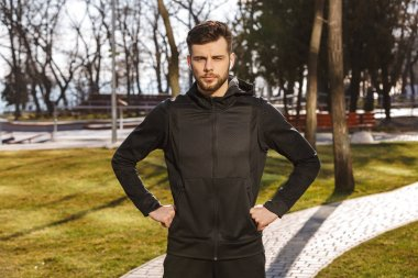 Portrait of a confident young sportsman in earphones standing outdoors