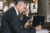 Fotografie Obrázek krásný kavkazské podnikatel na sobě bílou košili a černé šaty sedí u stolu v kanceláři při práci s dokumenty a notebook