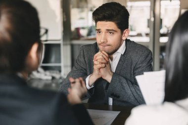 Business, career and placement concept - nervous uptight man 30s worrying and putting fists together during job interview in office with collective of specialists