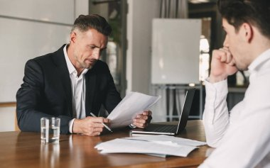 Business, career and placement concept - caucasian businessman negotiating with male candidate about work while reading his resume during job interview in office