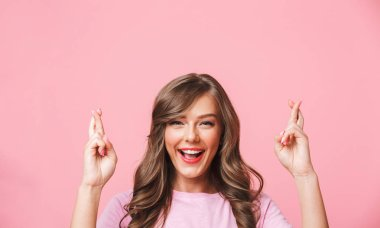 Closeup image of superstitious european woman in basic clothing keeping fingers crossed of both hands and dreaming for good luck isolated over pink background