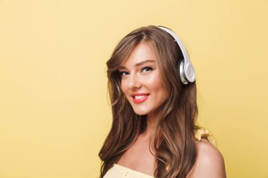 Photo of lovely smiling woman 20s with long brown hair enjoying listen to music via headphones isolated over yellow background