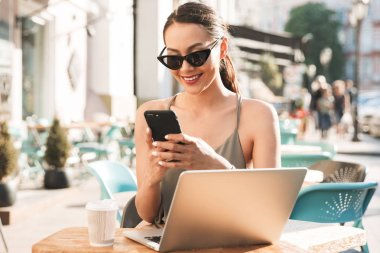 Image of happy caucasian woman wearing black sunglasses using smartphone while sitting in cozy cafe or restaurant outside in summer