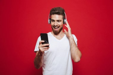 Photo of handsome excited young man in white t-shirt listening music with headphones isolated over red background using mobile phone.