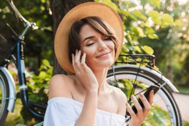 Close up of smiling young girl listening to music with mobile phone while sitting at the park with a bicycle