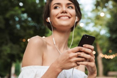 Cropped image of cheerful young girl listening to music with earphones and mobile phone while standing at the park