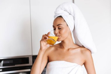 Healthy young asian woman wrapped in a shower towel drinking orange juice from a glass while standing on a kitchen