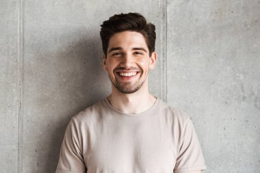 Image of happy young man standing over grey wall background looking camera.