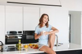 Směje se mladá žena pít kafe zatímco sedí v kuchyni doma ráno