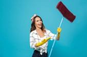 Fotografie z Černovlásky hospodyňka 20s v žluté gumové rukavice, usmívající se a držení mop při mytí podlahy izolovaná nad modrým pozadím