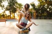 Két pozitív fiatal lányok érzik magukat, míg a lovaglás a gördeszka Park
