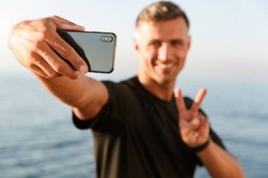 Smiling handsome shirtless sportsman taking a selfie while standing at the beach and showing peace gesture