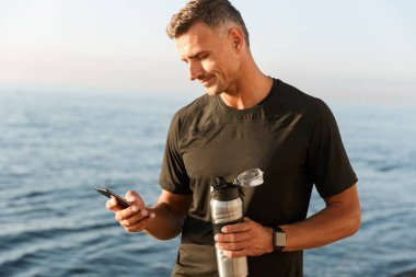 Smiling sportsman using mobile phone while standing at the beach and holding bottle of water