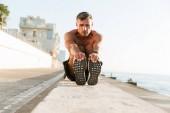 Fotografia Concentrati senza camicia sportsman in auricolari facendo esercizi di stretching in spiaggia