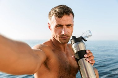 Confident handsome shirtless sportsman taking a selfie while standing at the beach and holding water bottle
