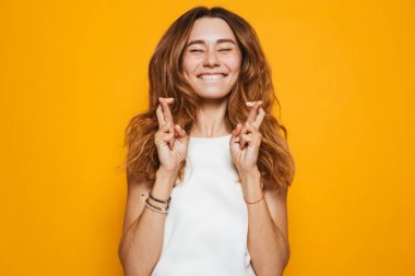 Portrait of an excited young girl holding fingers crossed for good luck isolated over yellow background