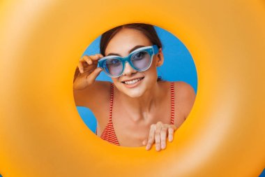 Portrait of a smiling young girl in swimsuit wearing sunglasses looking through inflatable ring hole isolated over blue background