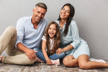 Portrait of a happy family father, mother, little daughter hugging while sitting together and laughing isolated over gray background