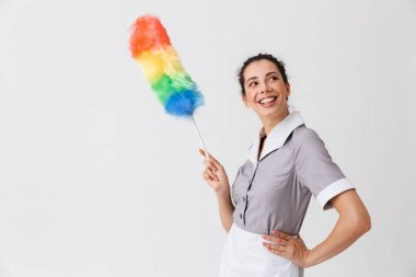 Portrait of a smiling young housemaid dressed in uniform holding a duster isolated over white background