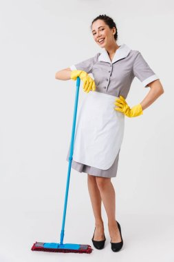 Full length portrait of a happy young housemaid dressed in uniform holding a mop isolated over white background