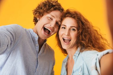 Portrait of two happy people man and woman laughing and taking selfie photo isolated over yellow background